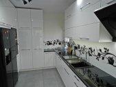 Rzut na białą kuchnie wykończoną na wysoki połysk